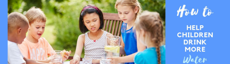 Children of all ages sitting around table drinking plain water