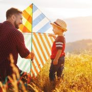 father flying a kite with his small son - be a healthy father
